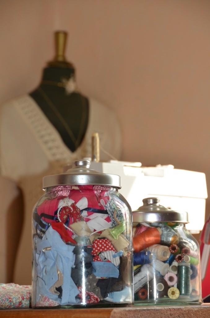 Le biais et les bobines dans de grosses bonbonnières transparentes et le mannequin de couture exposé